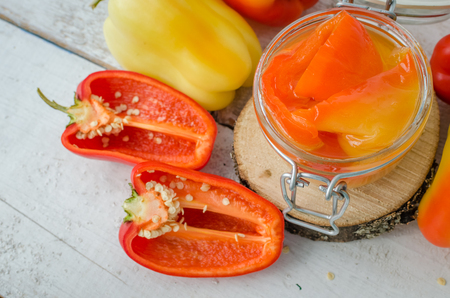 conserved: Bell pepper preserved in a glass jar with fresh peppers on white wooden background. Homemade marinated in oil red pepper. Glass jar with conserved roasted sweet paprika. Selective focus. Stock Photo