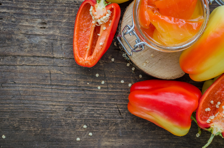 conserved: Bell pepper preserved in a glass jar with fresh peppers on old wooden background. Homemade marinated in oil red pepper. Glass jar with conserved roasted yellow and red paprika. Top view. Copy space.
