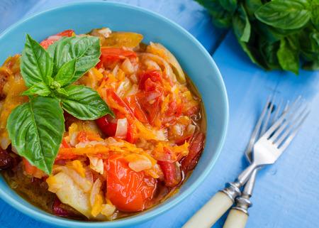Peperonata italiana: peperone arrosto con basilico in una ciotola su sfondo blu in legno. Pepe lecco stew ragout. Peperonata - piatto tradizionale della cucina italiana. Concetto di cucina italiana.