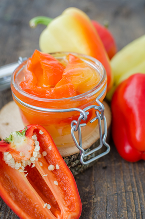 conserved: Bell pepper preserved in a glass jar with fresh peppers on old wooden background. Homemade marinated in oil red pepper. Glass jar with conserved roasted yellow and red paprika. Selective focus.