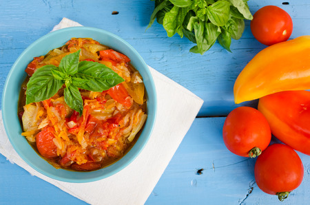 caper: Italian peperonata: roasted bell pepper with basil in a bowl on blue wooden background. Pepper lecho stew ragout. Peperonata - traditional dish of italian cuisine. Italian cuisine concept. Top view.