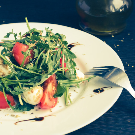 Fresh summer salad with tomatoes, fresh arugula leaves, mini mozzarella cheese and sesame seeds on white plate over dark wooden baclground. Healthy diet food concept. Selective focus.
