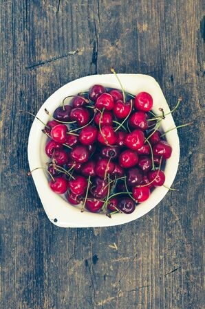 Red ripe juicy cherry in metal plate on rustic wooden background. Sweet summer berries. Freshly harvested merry. Directly above. Top view. Copy space.