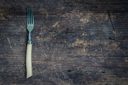 grunge silverware: Rustic fork on old wooden shabby background for your project. Copy space. Top view.