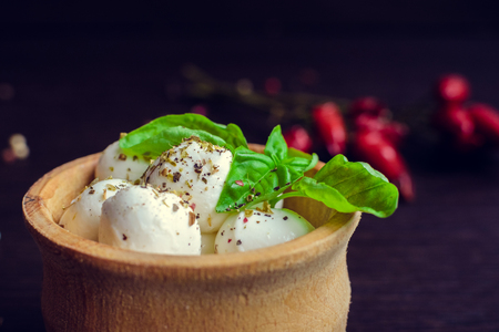 Fresh mini Mozzarella ?heese with basil in wooden plate on dark background with chili pepper. Selective focus. Stock Photo