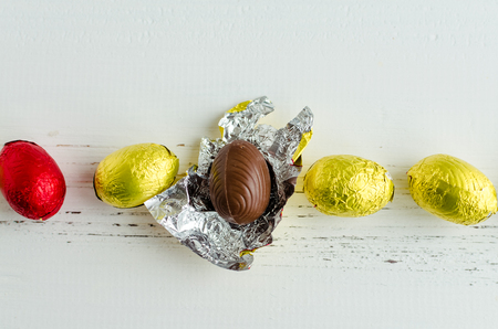 Easter composition with yellow and red chocolate eggs on white shabby chic wooden background. Stock Photo