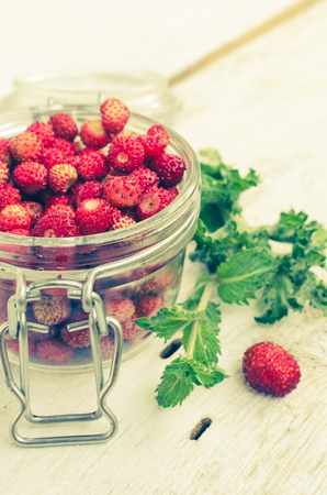 Wild strawberry in glass jar with green mint leaves on white rustic wooden background. Sweet berry Fragaria for summer dessert. Healthy snack. Selective focus. Stock Photo