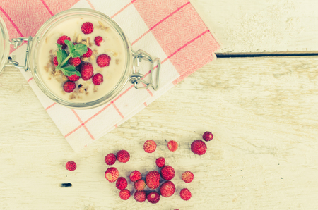Fresh milk yoghurt with wild strawberries and granola served in a glass jar with mint leaves on white wooden table with striped red napkin. Healthy summer breakfast concept. Top view. Copy space.