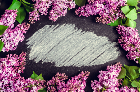 Frame of beautiful spring flowers lilac on chalkboard background with place for text. Syringa vulgaris. Happy Mothers Day greetings card. Top view. Copy space.