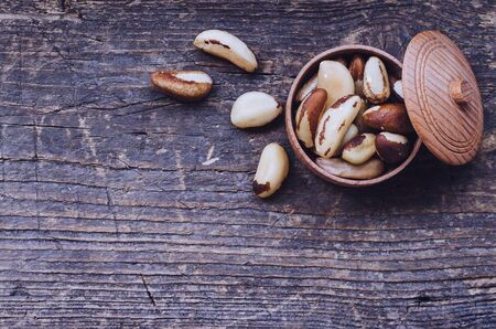selenium: Tasty Brazil nuts from Bertholletia excelsa tree in wooden bowl on the old background with place for text. Healthy edible seeds food ingredient on the table. Top view. Copy space.