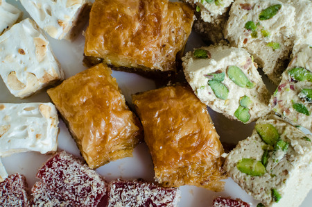 Assorted traditional eastern desserts on a white wooden background. Baklava, halva, rahat lokum, sherbet, nuts, dates, kadayif on plates. Top view. Close up.
