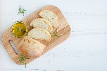 Sliced freshly baked ciabatta bread on wooden cutting board on white rustic table with rosemary, salt and olive oil. Italian food concept. Top view. Copy space.