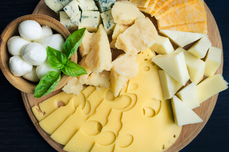Cheese plate: Parmesan, cheddar, gouda, mozzarella and other with basil on wooden board on dark background. Tasty appetizers. Top view.