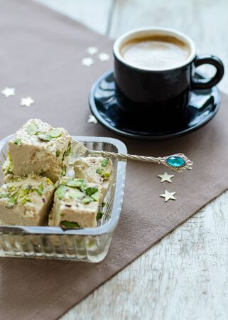 Traditional eastern dessert - halva pistachio and cup of coffee. Arabian sweets on wooden table. Turkish delight concept.