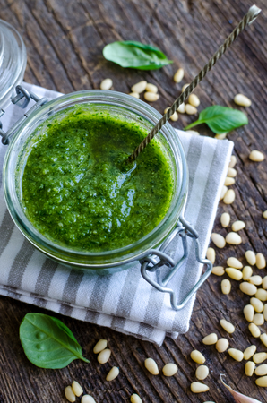 Pesto genovese - traditional Italian green basil sauce with pine nuts, basil and garlic on rustic wooden background. Top view. Stock Photo