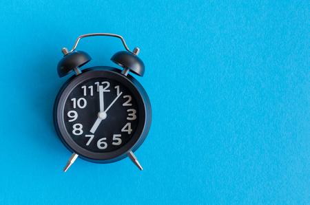 7 テキストのミニマルなレトロなポップなアート スタイルに青色の背景に目覚まし時計。コンセプトを覚ます。学校に戻る領域をコピーします。平