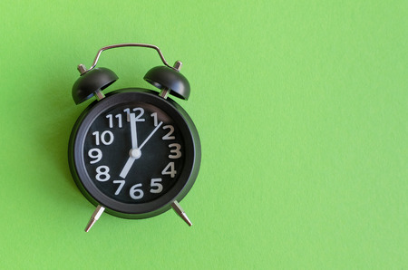 Alarm clock with seven oclock on green background in minimalistic retro pop art style with place for text. Wake up concept. Back to school. Copy space. Top view.