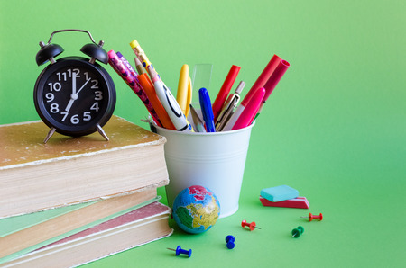 Back to school concept with stationery. School supplies on green background in pop art style. Schoolchildren and students studies accessories with books, clock and globe. Stock Photo