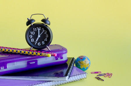 Back to school concept with stationery. School supplies on yellow background in pop art style. Schoolchildren and students studies accessories with notebooks, clock and globe.