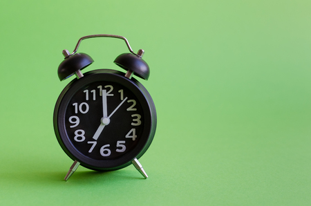 Alarm clock with seven oclock on green background in minimalistic retro pop art style with place for text. Wake up concept. Back to school. Copy space.