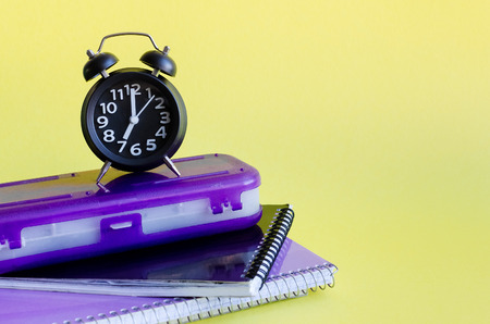 Back to school concept with stationery. School supplies on yellow background in minimalistic pop art style. Schoolchildren and students studies accessories with notebooks and clock. Copy space. Stock Photo
