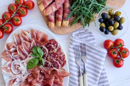 Table full of mediterranean appetizers, tapas or antipasto. Assorted Italian food set. Delicious snack on party or picnic time. Chopping board with meat. Italian style banquet. Top view. Stock Photo