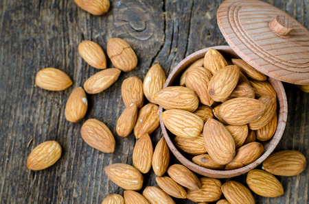 selenium: Tasty almonds nuts in wooden bowl on the old background. Healthy edible seeds food ingredient on the table. Top view.