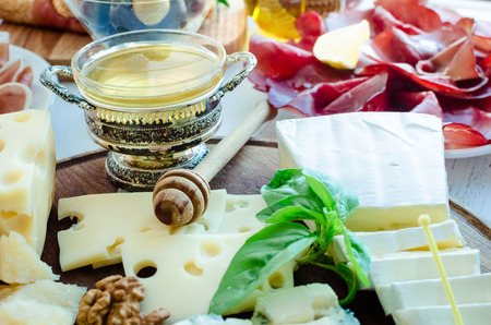 Cheese platter: Brie, Parmesan, cheddar, gouda, gorgonzola and other with walnuts and honey on wooden board. Tasty appetizers with different kind of cheese. Delicious snack on party or picnic time.