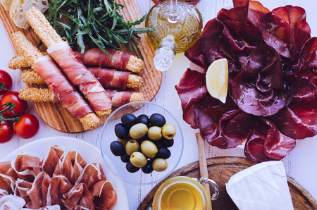 Table full of mediterranean appetizers, tapas or antipasto. Assorted Italian food set. Delicious snack on party or picnic time. Chopping board with meat and cheese. Italian style banquet. Top view. Stock Photo