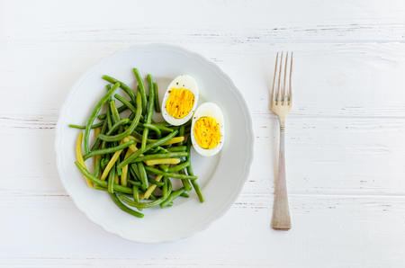 Cooked green beans with boiled eggs in white plate. Healthy vegetarian food concept. Top view.