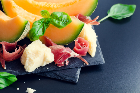 Concept of italian food with melon and prosciutto on dark background. Traditional appetizer antipasto. Selective focus. Stock Photo