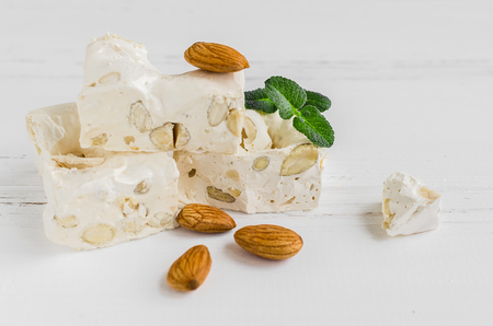 Sweet nougat with almonds on white wooden background. Pieces of white nougat.