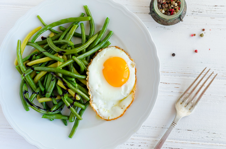 Cooked green beans with sauce balsamico glassa and fried egg in white plate on wooden background with fork. Healthy vegetarian food concept. Top view. Stock Photo