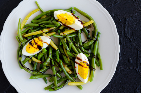 Fresh summer warm salad with cooked green beans with boiled eggs and sauce balsamico glassa in white plate on black stone background. Healthy eating. Vegetarian food concept. Top view. Stock Photo