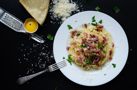 Pasta Carbonara. Spaghetti with bacon, parsel and parmesan cheese. Pasta Carbonara on white plate with parmesan on dark background. Italian food concept. Top view.