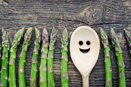 Row of fresh organic green asparagus and wooden spoon with smiley face on an old wooden background. Happiness and healthy food concept. Top view.
