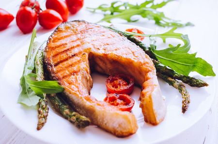 grill: Grilled salmon steak with asparagus, tomatoes cherry and arugula on a plate on white wooden background. Healthy lunch concept. Delicious, nutritious eating. Close up.
