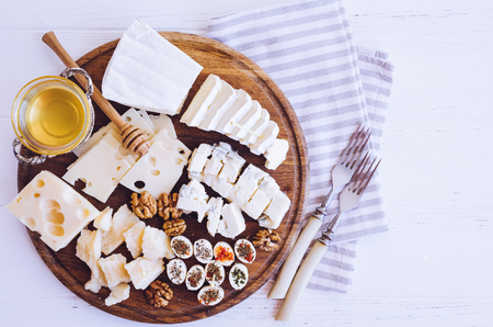 Cheese platter: Parmesan, cheddar, gouda, gorgonzola, brie and other with walnuts and honey on wooden board on white background. Tasty appetizers with different kind of cheese. Top view.