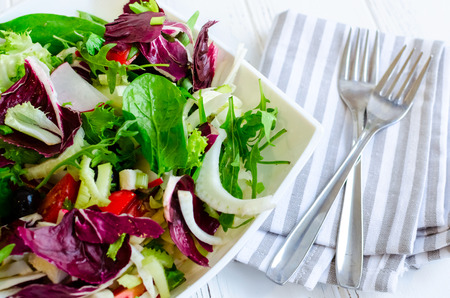 Fresh summer green salad mix with salad lettuce, spinach, fennel, celery, tomatoes, radish, olives, chicory and arugula in white bowl with forks. Healthy eating concept. Vegetarian vegan food. Stock Photo