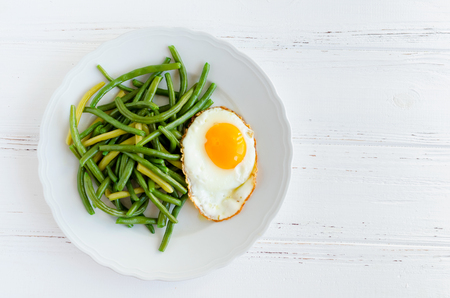 Cooked green beans with fried egg in white plate on wooden background with space for text. Healthy vegetarian food concept. Top view. Copy space.