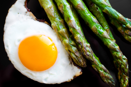 Fried egg and roasted fresh asparagus in black plate. Healthy lunch concept. Delicious, nutritious eating. Top view.