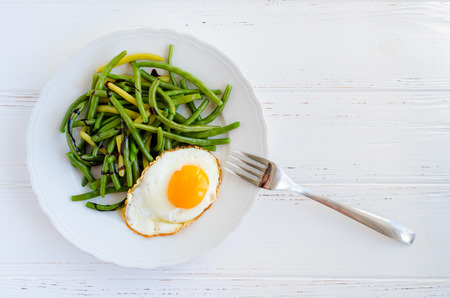Cooked green beans with sauce balsamico glassa and fried egg in white plate on wooden background with space for text. Healthy vegetarian food concept. Top view. Copy space.
