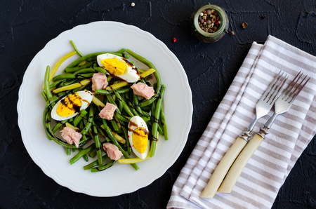 Fresh summer warm salad with cooked green beans, tuna, boiled eggs and sauce balsamico glassa in white plate on black stone background. Healthy eating concept. Top view. Stock Photo