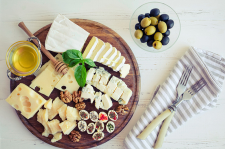 Cheese platter: Parmesan, cheddar, gouda, gorgonzola, brie and other with walnuts, olives and honey on wooden board on white background. Tasty appetizers with different kind of cheese. Top view.