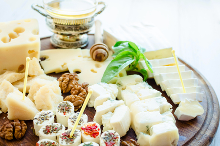 Cheese platter: Parmesan, cheddar, gouda, gorgonzola, brie and other with walnuts and honey on wooden board on white background. Tasty appetizers with different kind of cheese.