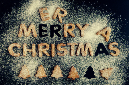 Wording Merry Christmas from homemade gingerbread cookies on dark chalkboard background. Christmas concept. Christmas moody style greetings card. Happy New Year. Top view.