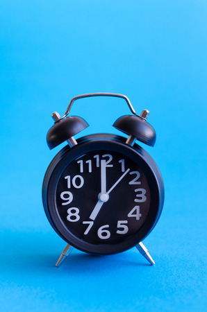 Alarm clock with seven oclock on blue background in minimalistic retro pop art style with place for text. Wake up concept. Back to school. Copy space.