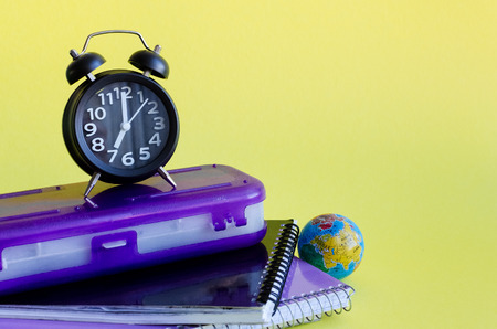 Back to school concept with stationery. School supplies on yellow background in pop art style. Schoolchildren and students studies accessories with notebooks, clock and globe. Copy space.