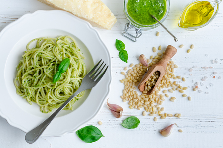 Spaghetti with homemade pesto sauce on white wooden table. Pasta with pesto alla genovese. Italian cuisine concept. Top view.