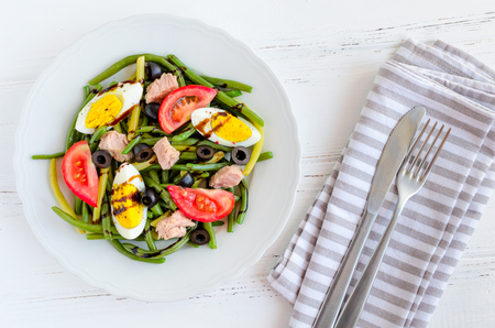 Summer warm salad with cooked green beans, tuna, tomatoes, boiled eggs and sauce balsamico glassa in white plate with knife and fork on wooden background. Healthy eating concept. Top view. 스톡 콘텐츠